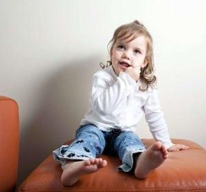 ילדה יחפה מחזיקה אצבעות בפה ומחייכת