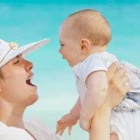 אמא-מחזיקה-תינוק-בידיים-ומניפה-אותו-על-רקע-ים_1200X600